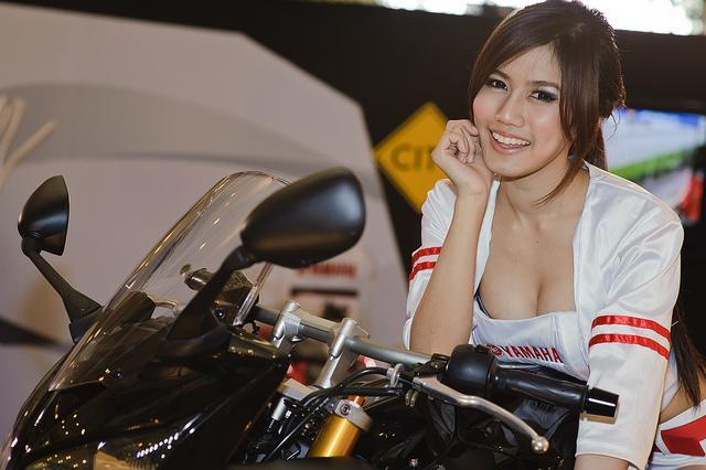 Asiatische Frau auf einem schwarzen Motorrad