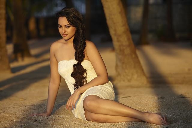Die schöne indische Schauspielerin Sonakshi Sinha im Sand liegend
